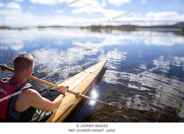 Young man canoeing, Norrbotten, Sweden