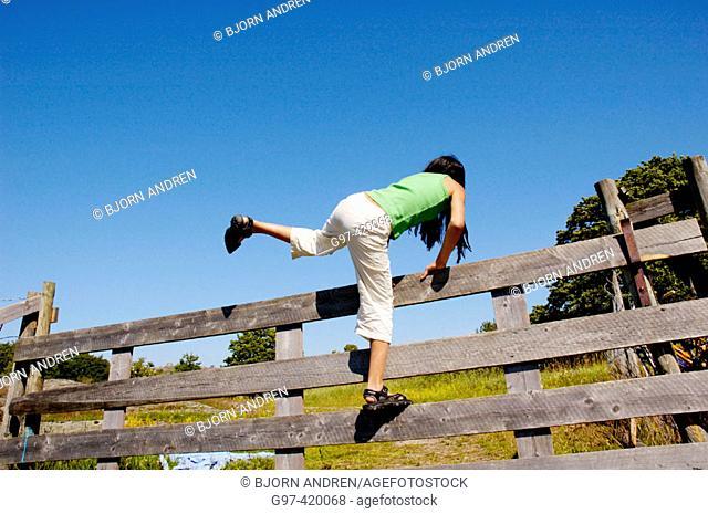 Girl climbing over a fence