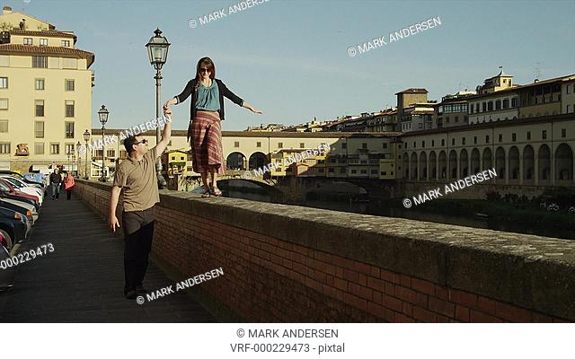 MS Man assisting woman walking on top of waterfront ledge with Ponte Vecchio in background / Florence,Tuscany,Italy