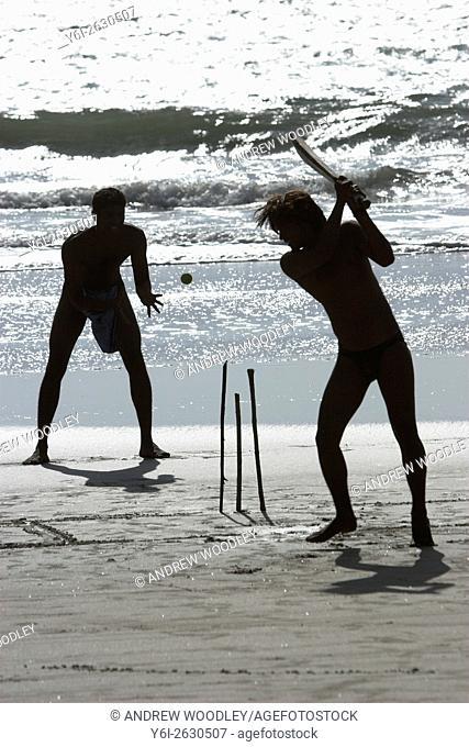 Beach cricket with bat sticks for stumps and tennis ball Fatrade Beach south Goa India
