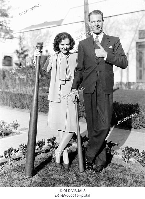 Couple standing together with one oversized baseball bat All persons depicted are not longer living and no estate exists Supplier warranties that there will be...