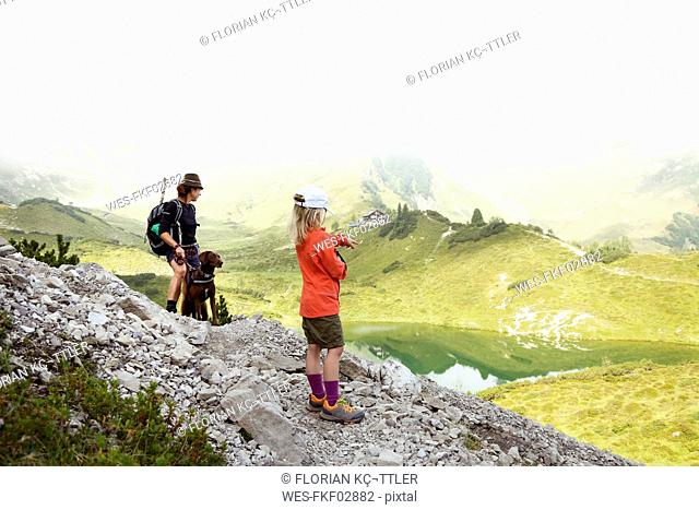Austria, South Tyrol, mother, daughter and dog on hiking trail