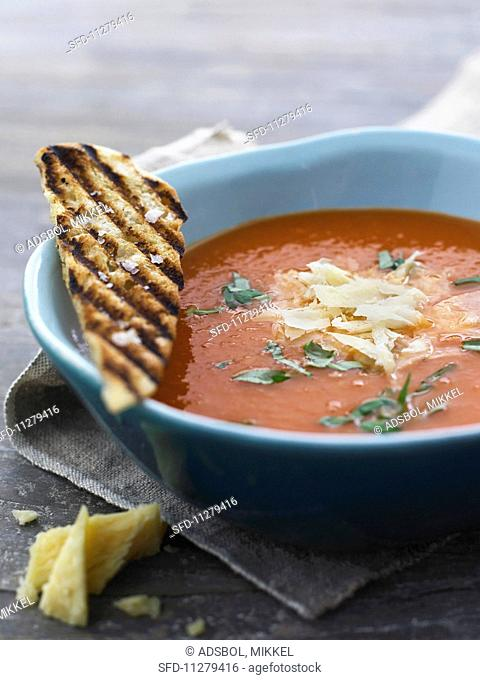 Tomato soup with parsley, grated cheese and croutons