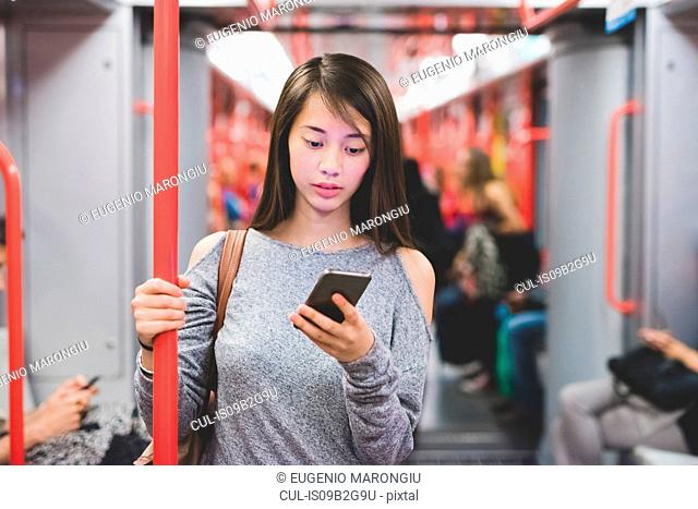Young woman traveling on train carriage reading smartphone texts