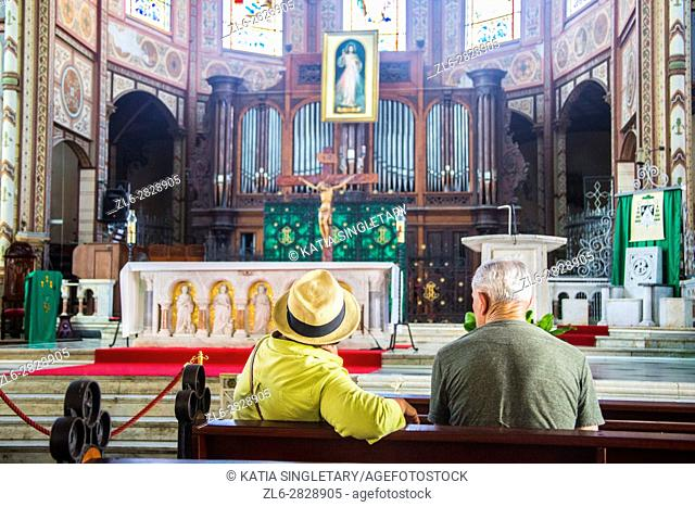An older couple senior mature with white hair and a hat sitting on a bench in a catholic church