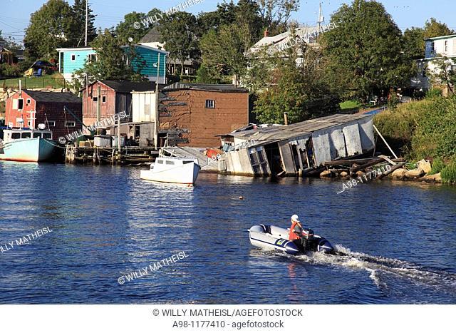 speeding motor boat destroyed fish shack at old traditional fishing village Herring Cove, Nova Scotia, Atlantic Canada, North America