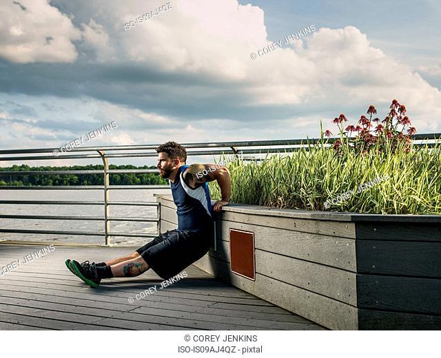 Young man doing push ups against lake pier seat