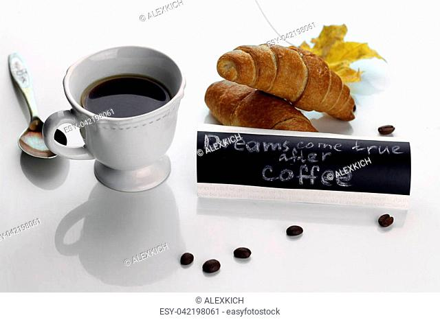 breakfast consisting of hot black coffee and fresh croissants on a table