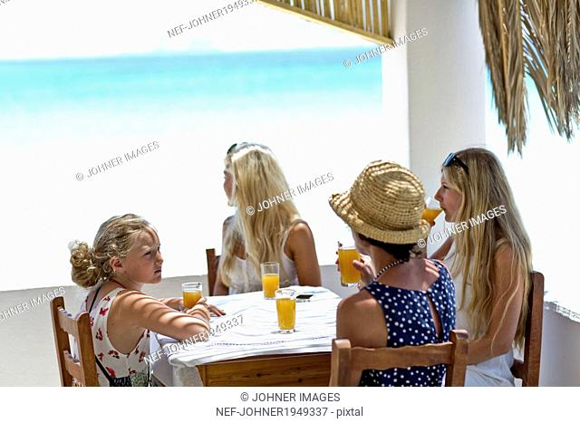 Mother with daughters drinking juice on patio, Greece