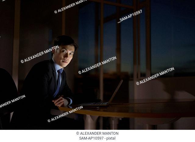 Singapore, Businessman sitting at desk with laptop