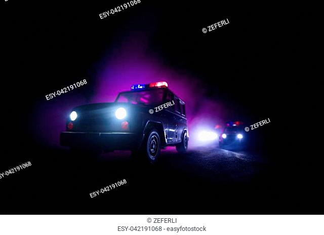 speed lighting of police car in the night on the road. Police cars on road moving with fog. Selective focus