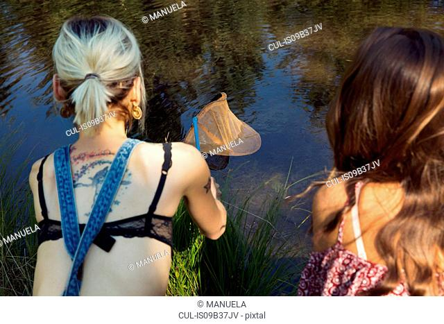 Rear view of two female friends fishing from river bank, Sattelbergalm, Tyrol, Austria