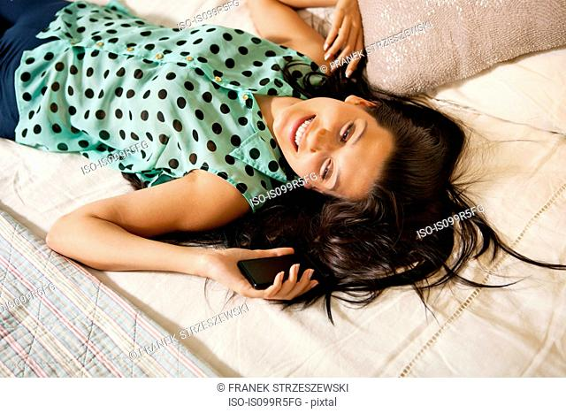 Young woman on bed with smartphone, high angle