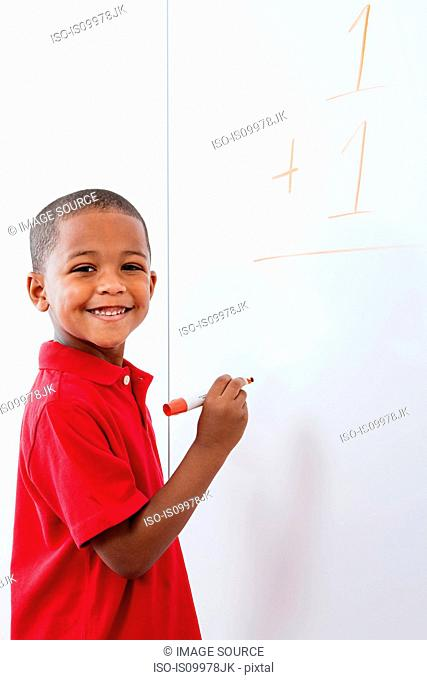 Boy with sum on whiteboard