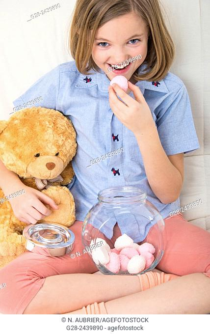 Little girl eating sweets and cuddling her teddy bear