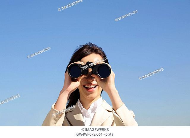 Japan, Honshu, Tokyo, Young businesswoman looking through binoculars, close-up