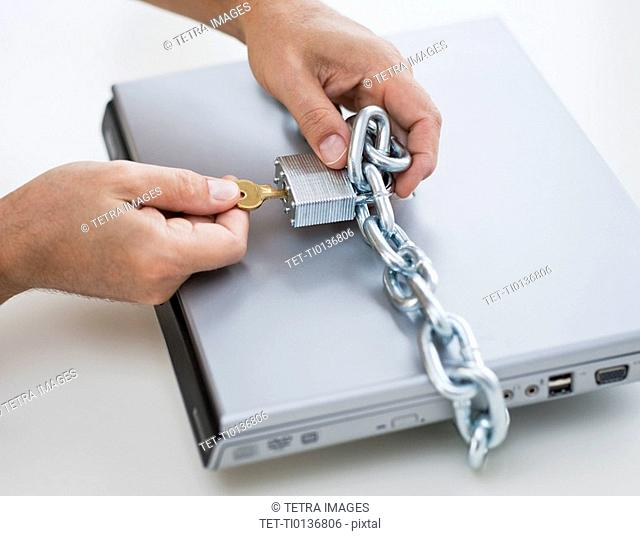 Hands placing lock and chain on computer