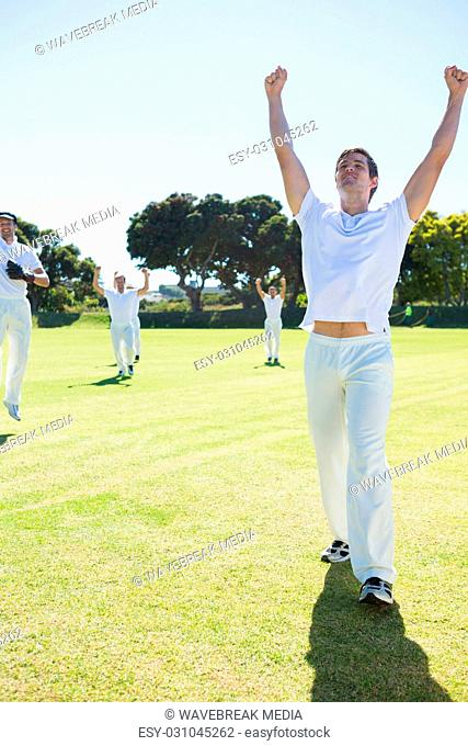 Happy cricket players enjoying victory while standing on field