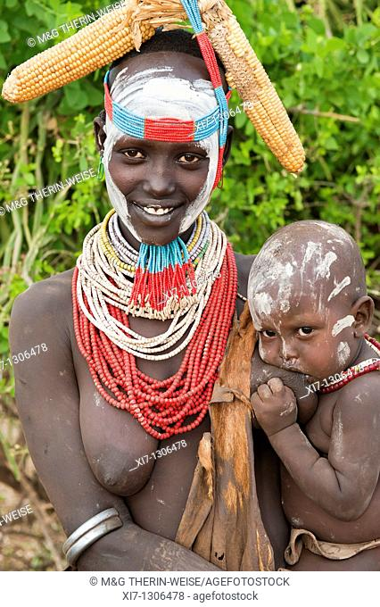 Young Karo woman with lots of colorful necklaces and corn on the head holding a suckling baby, Omo river valley, Southern Ethiopia