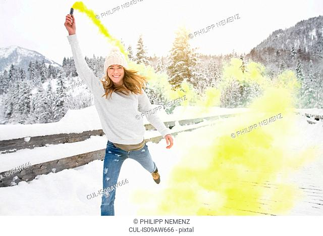 Woman playing with coloured smoke flare, Alps, Germany