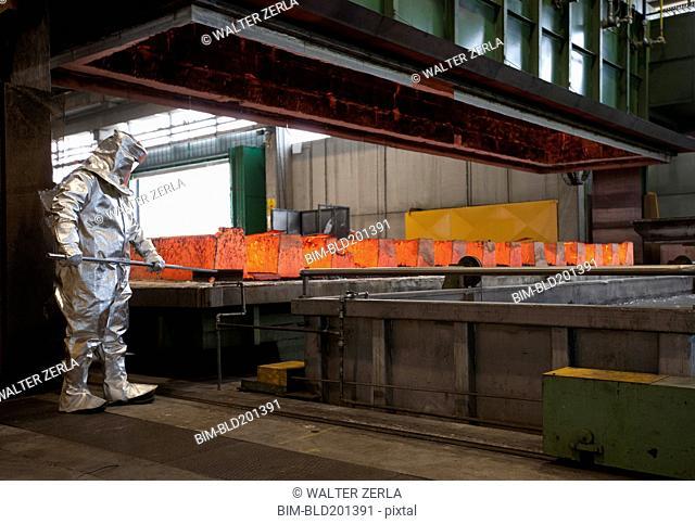 Worker working with hot metal in steel factory