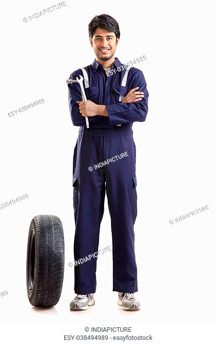 Portrait of car mechanic with spare tyre