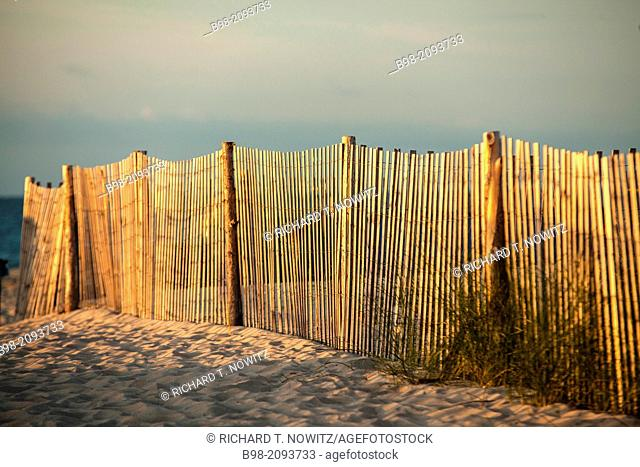A fence in the sand dunes in Cape May, is lit be the first rays of the sun. The fence is used to prevent beach and dune erosion