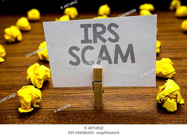 Word writing text Irs Scam. Business concept for targeted taxpayers by pretending to be Internal Revenue Service Clothespin hold holding paper idea reminder...