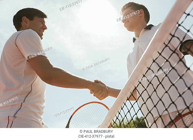 Young male tennis players handshaking in sportsmanship at net