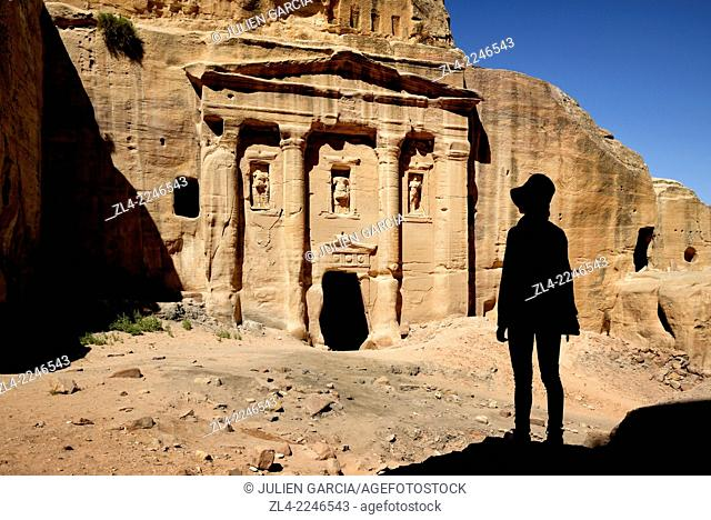 Silhouette of a woman watching the façade of the Roman Soldier's Tomb, carved out of a sandstone rock face. Jordan (Hashemite Kingdom of)