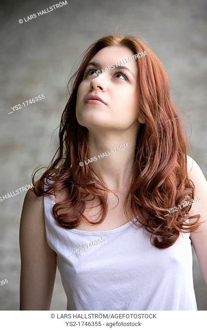 Portrait of a pensive young woman with red hair looking up