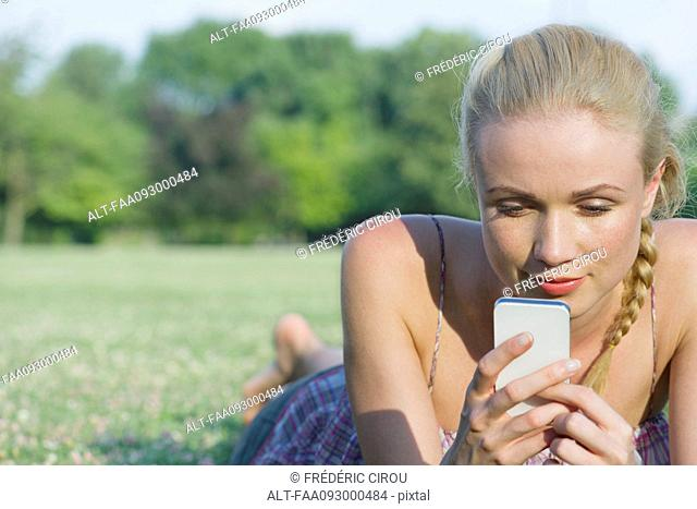 Woman lying on grass using smartphone