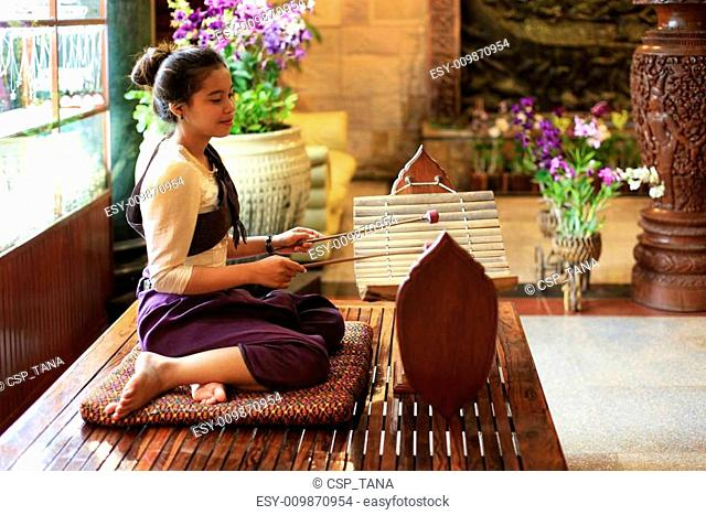 PHNOM PENH, CAMBIDIA - APRIL 6, 2014: Unidentified local girl plays in traditional gamelan instruments outside hotel on April 06, 2014 in Phnom Penh, Cambodia