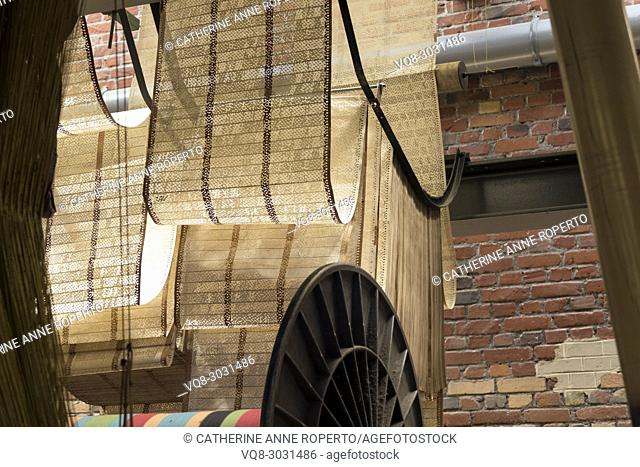 Waterwheel formation of looped perforated pattern punch cards tumbling over an iron spoked wheel with the brickwork behind mimicking the punched card patterns