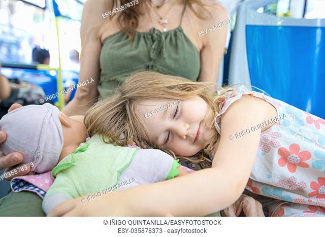 three years old blonde girl sleeping hugging doll on mother legs sitting on the bus