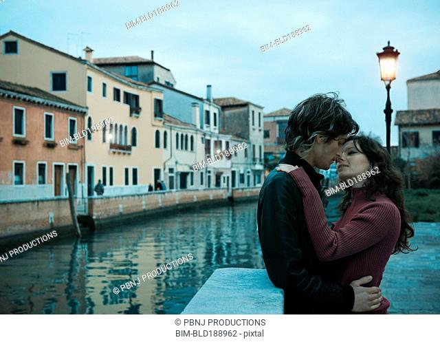 Italian couple kissing near canal