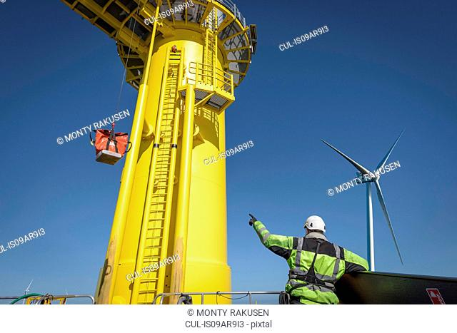 Engineer winches parts up to wind turbine from boat on offshore wind farm