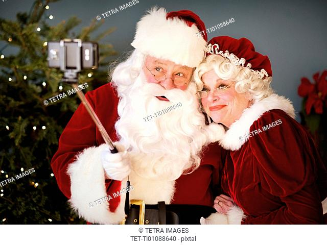 Santa and Mrs. Santa taking selfie with monopod