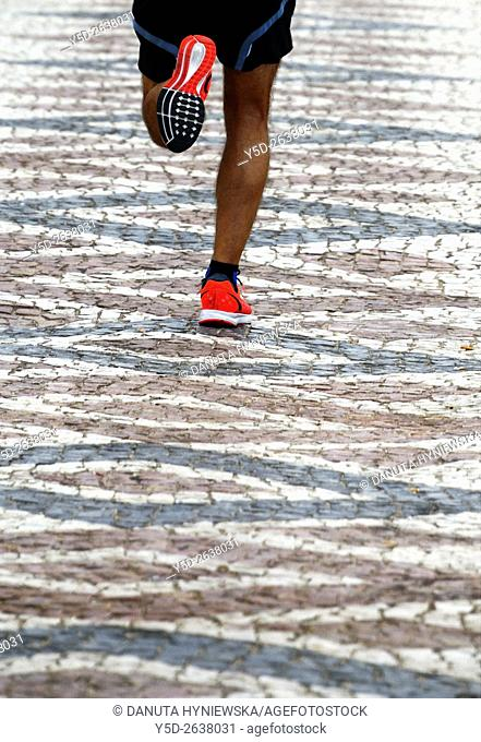 Avenida dos Descobrimentos, man running, cobbled street, Lagos, Algarve, Portugal