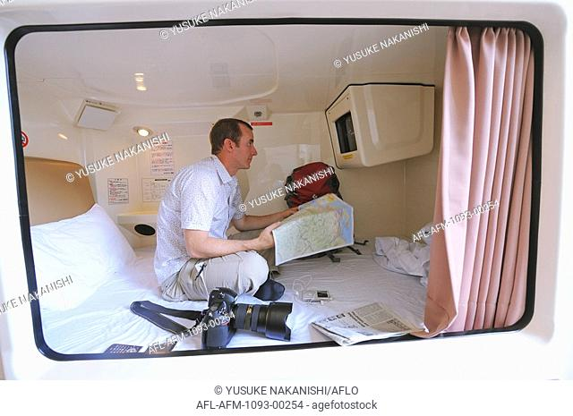 Man sitting in pod of capsule hotel
