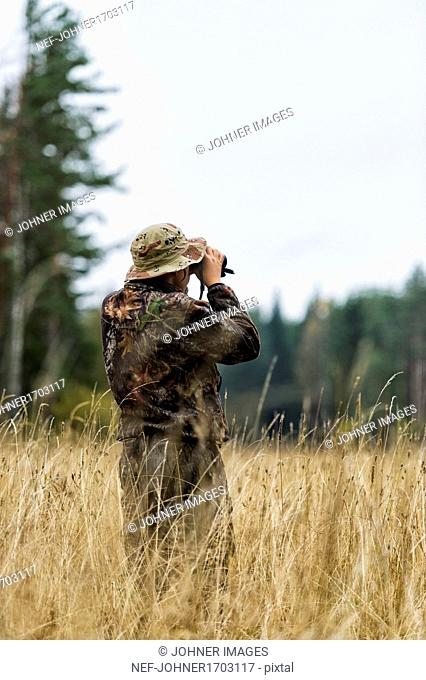 Teenager with binoculars watching forest
