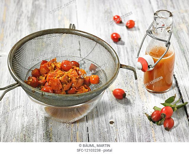 Rose hip juice in a bottle with pitted and boiled rose hips in a strainer