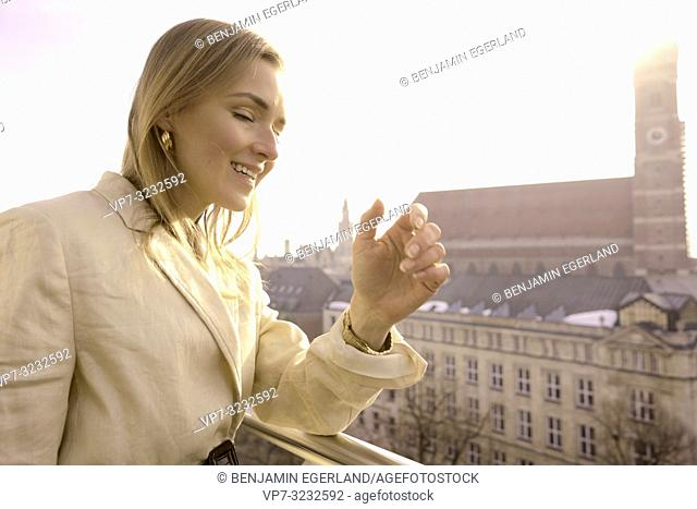 fancy blogger woman on balcony next to church Frauenkirche, Marienkirche, in city Munich, Bavaria, Germany