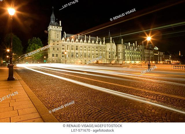 Moving traffic lights passing by the Conciergerie on Pont au Change at night. Paris. France