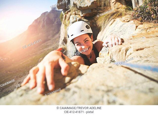 Portrait smiling, confident rock climber reaching for rock