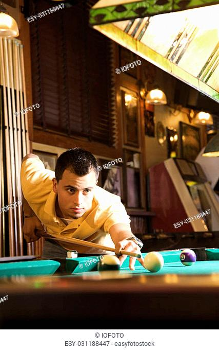 Young man concentrating while aiming at pool ball while playing billiards