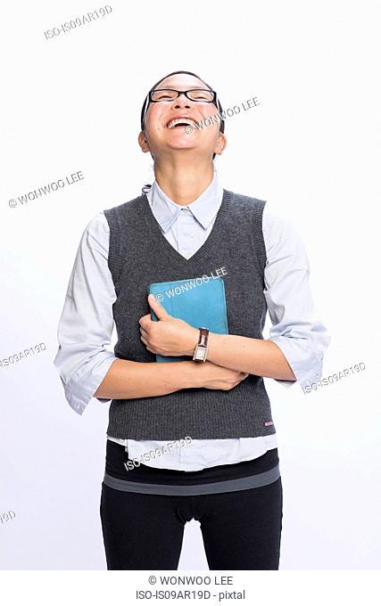 Businesswoman hugging digital tablet, laughing
