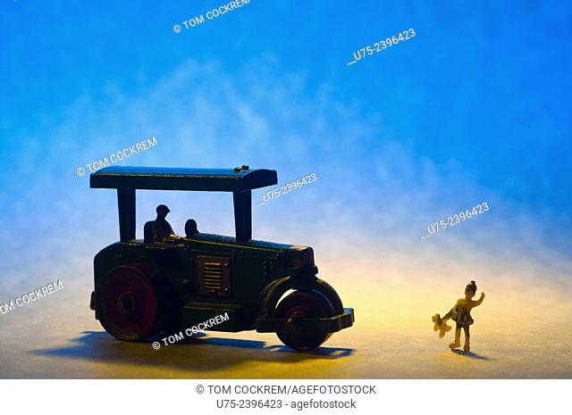 Miniature toy steamroller with mini figure of girl in studio setting