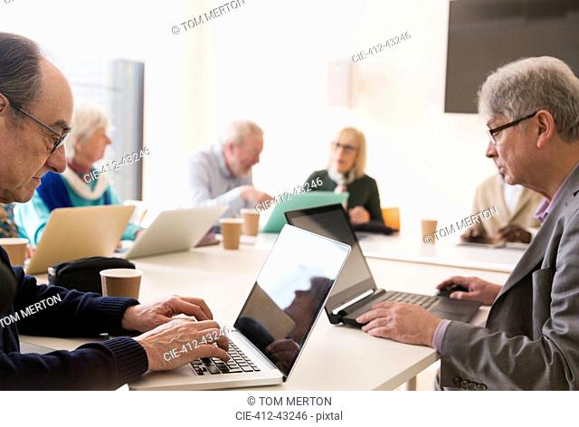 Senior businessmen using laptops in conference room meeting