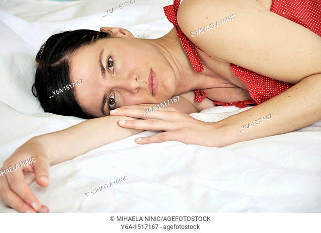 Portrait of a beautiful young woman lying on bed